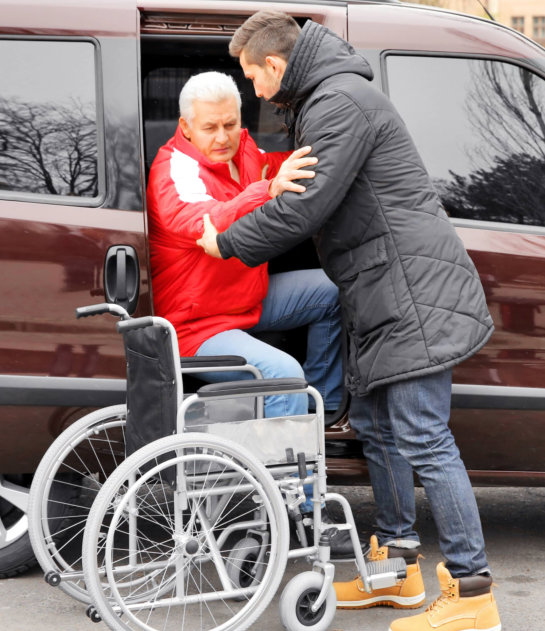 caregiver assisting old man getting in the car