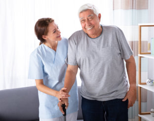 caregiver assiting old woman to walk