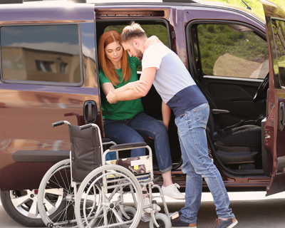 a driver assisting a patient to her tranportation