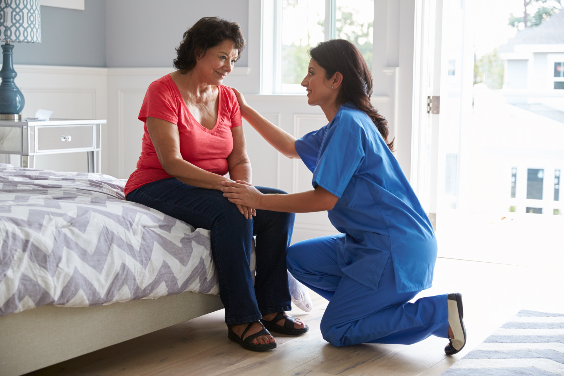 a caregiver and a senior woman smiling at each other