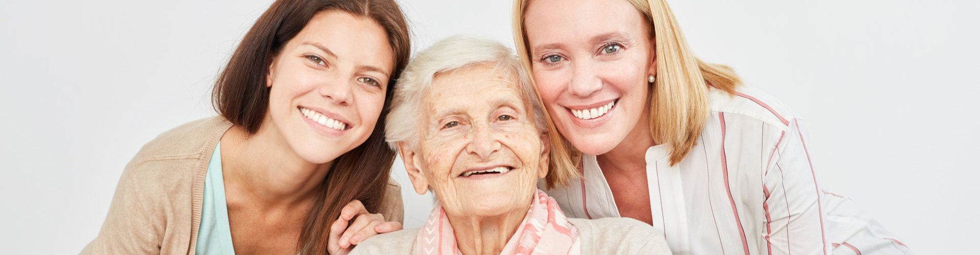 caregivers and old woman smiling